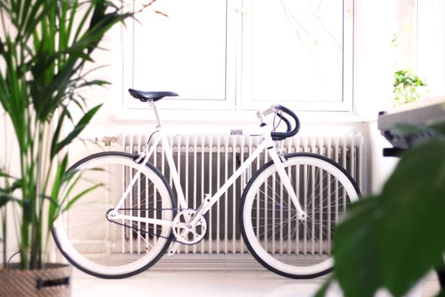 white bicycle in front of a large radiator with two houseplants in the foreground.