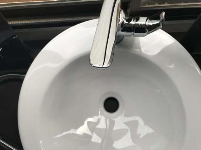White porcelain round sink with silver faucet viewed from above.