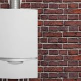 Tankless water heater against a brick wall.