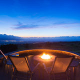 Chairs arranged around a fire pit on a patio overlooking a sunset.